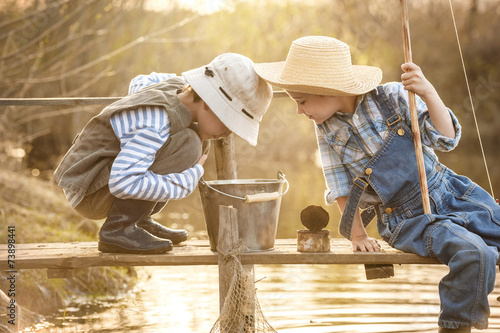 Boy fishes on a bridge on the lake