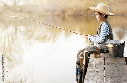 Printed kitchen splashbacks Fishing Boy fishes on a bridge on the lake