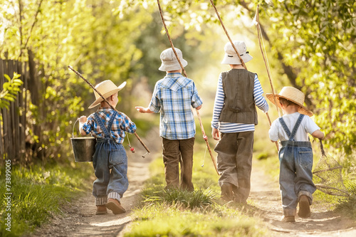 Poster de jardin Peche Boys go fishing with fishing rods on a rural street