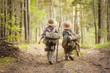 Leinwandbild Motiv Boys on a forest road with backpacks