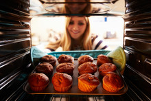 Woman Taking Tray Of Baked Muffins Out Of The Oven