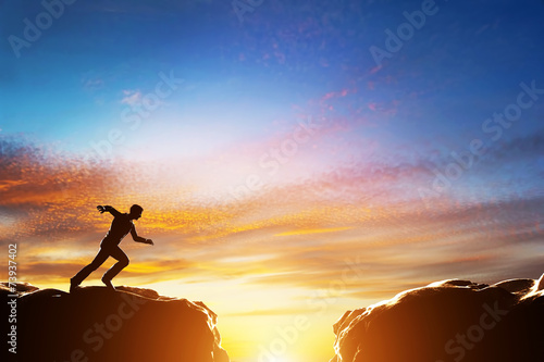 Fototapeta Man running fast to jump over precipice between two mountains