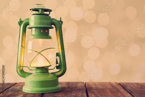 Lantern on wooden table on bright background Poster