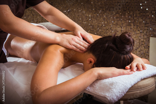 Poster Artist KB Masseur doing massage on woman body in the spa salon.