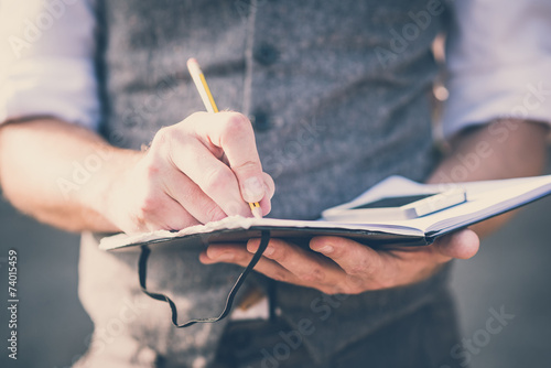Fotografía  close up hands man writing on diary and smartphone