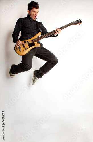 Valokuva  Jumping bass player on a white background