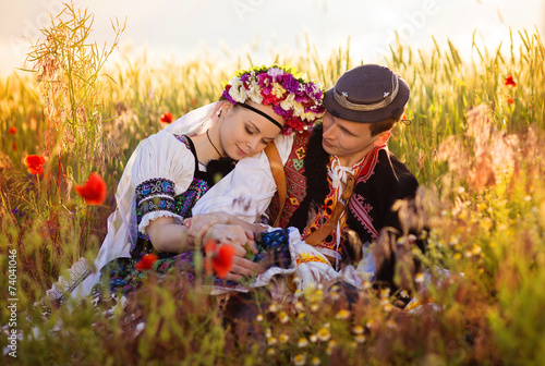 Leinwand Poster Couple in love with traditional folk costumes