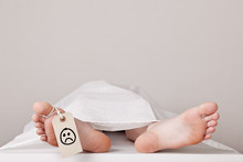 Dead Body In The Morgue With A Sad Smiley Attached To The Toe