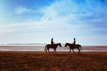 Couple Silhouettes On The Beach With Horses