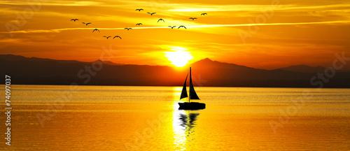 Fotografia  puesta de sol panoramica en el mar con un velero