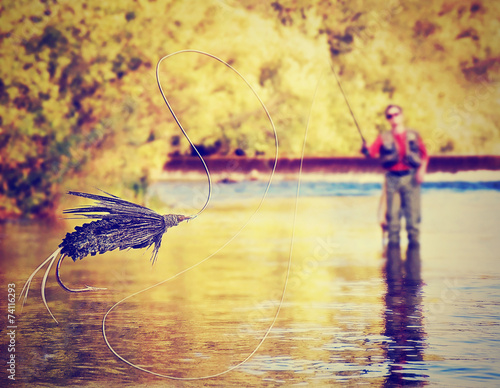 Tablou Canvas a person fly fishing with a big trout in front