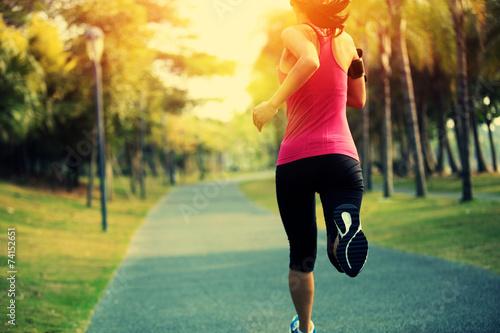 Fototapeta woman runner running at tropical park obraz