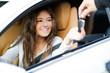Leinwandbild Motiv Young woman receiving the keys of her new car