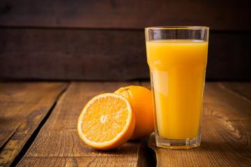 Fototapeta Orange fruit and glass of juice on brown wooden background