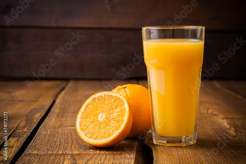 Poster Sap Orange fruit and glass of juice on brown wooden background