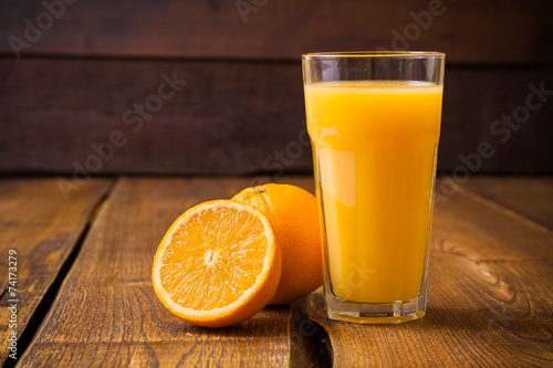 Foto op Canvas Sap Orange fruit and glass of juice on brown wooden background