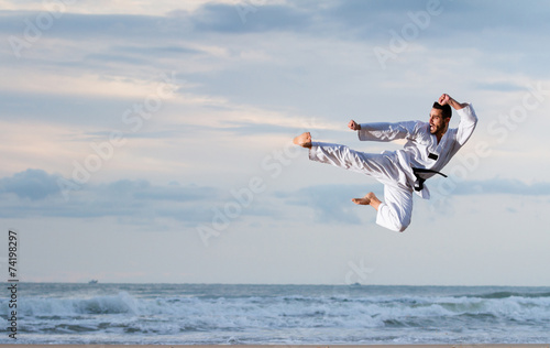 Tuinposter Vechtsport Man jumping to practice Marcial Arts kick