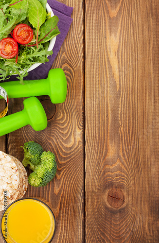 Foto op Plexiglas Fitness Dumbells, tape measure and healthy food over wooden background