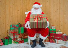Santa Claus In His Grotto Holding A Gift Wrapped Present