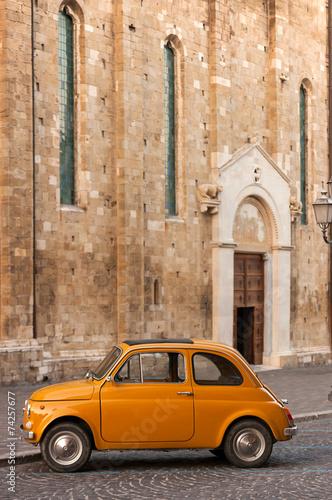 stary-wloski-pomaranczowy-samochod-przed-kosciolem-katolickim