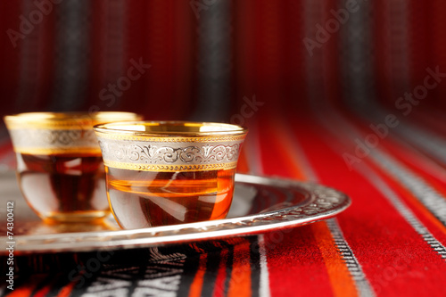 In de dag Midden Oosten A tray of Arabian tea cups is placed on Arabian woven fabric