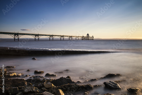 Long exposure landscape image of pier at sunset in Summer