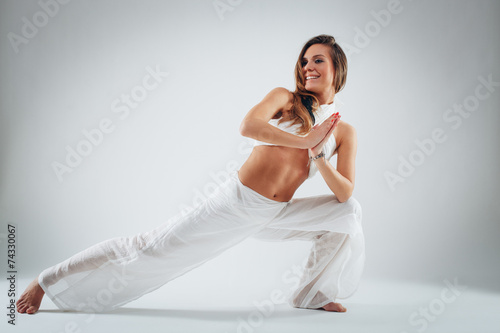 Vászonkép  Young woman in yoga pose in studio on white background