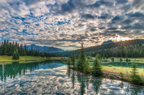 Fototapete - Amazing Clouds and Trees Reflected in Lake