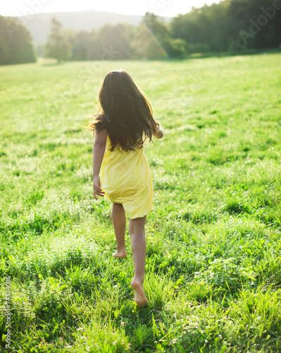 6aadb2a13290c8 Mädchen in gelbem Kleid läuft in Wiese