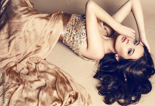 Photo  beautiful brunette in luxurious sequin beige dress