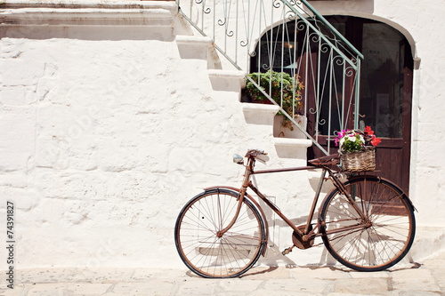 Aluminium Prints Bicycle Old bicycle with a basket leaning against a wall in Italy