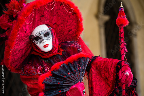 Woman in typical red dress poses during Venice Carnival