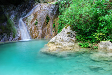 Natural pool with azure water and a small waterfall