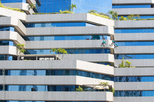 Fotografie, Obraz  Man cleaning windows on a high rise building