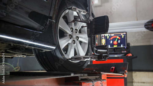 Photo Car on stand with sensors on wheels for wheels alignment camber