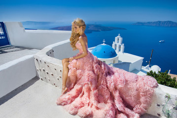 Beautiful blond woman with long legs in a pink ball gown