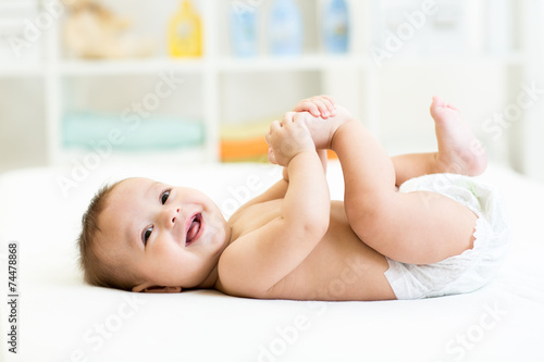 baby lying on white bed and holding legs Fototapet