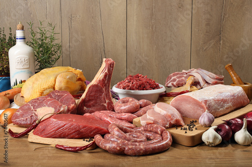 Foto op Aluminium Vlees carne cruda gruppo su tavolo di legno