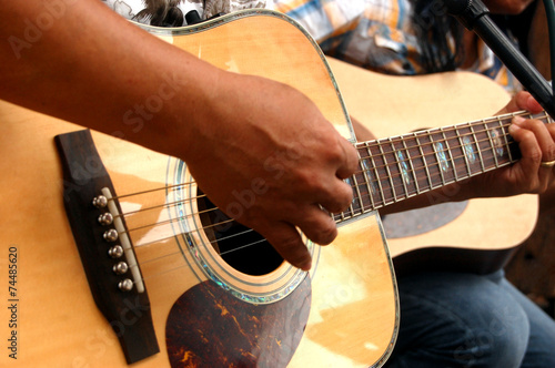 Photo  Two people playing an acoustic guitar