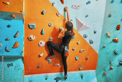 Fototapeta Woman climbing up on practice wall obraz