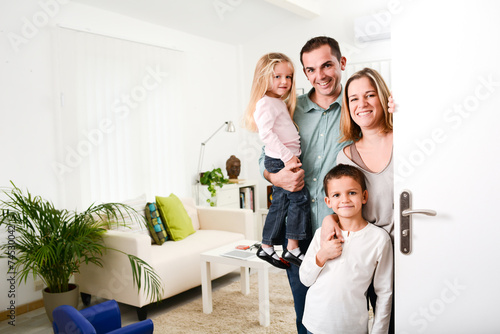 Photo happy family with young kids welcoming a guests at home doorh