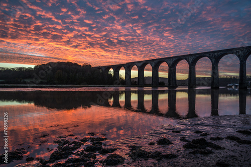Photo  Sunrise on the lynher with red sky and the viaduct ,cornwall, uk