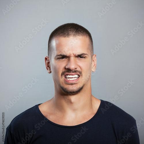 Fotografie, Tablou  Studio shot of a young man grimacing