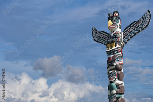 фотография Totem wood pole in the blue cloudy background