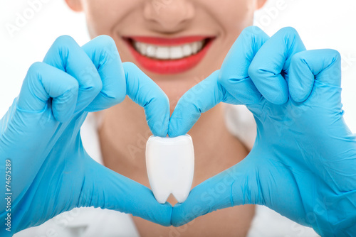 Valokuva  Portrait of dentist with tooth on white background