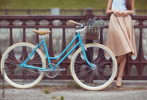 Fotografia  Młoda piękna, elegancko ubrana kobieta z rowerem