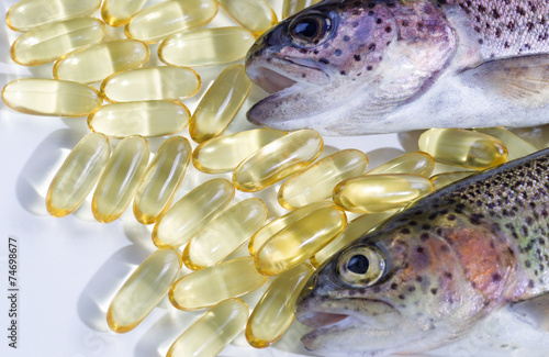 Valokuva  Fish oil capsules with fresh fish on white background