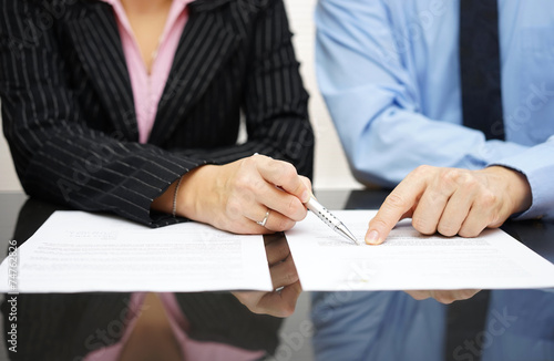 Fotografia  businessman and businesswoman are pointing to .article of the tr