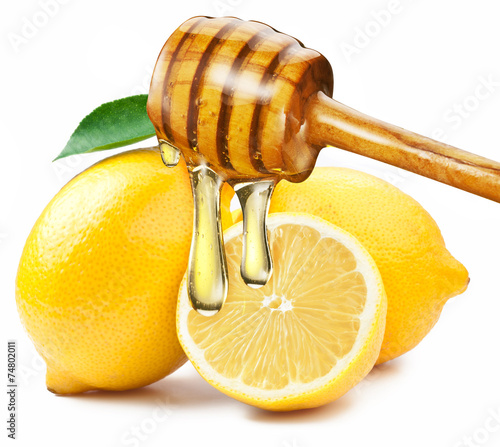 Honey with wood stick pouring onto a slice of lemon. Canvas Print