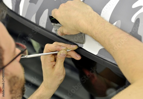 Fotografía  Car wrapping specialist wraps a car parts with adhesive foil